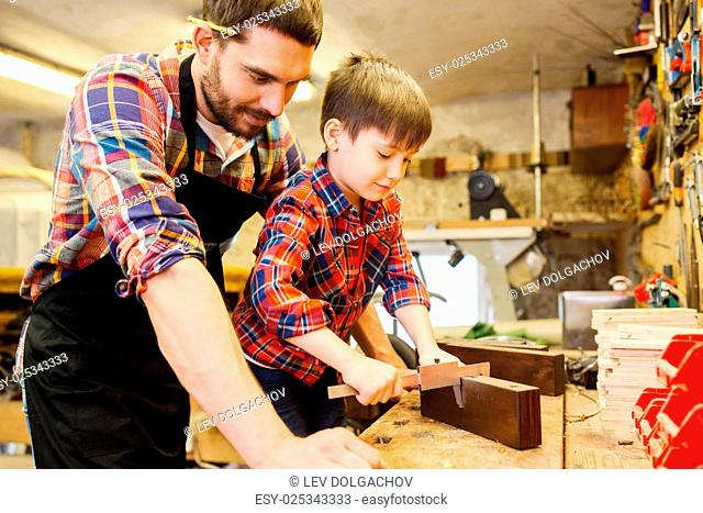 family, carpentry, woodwork and people concept - father and little son with calipers measuring wood plank at workshop