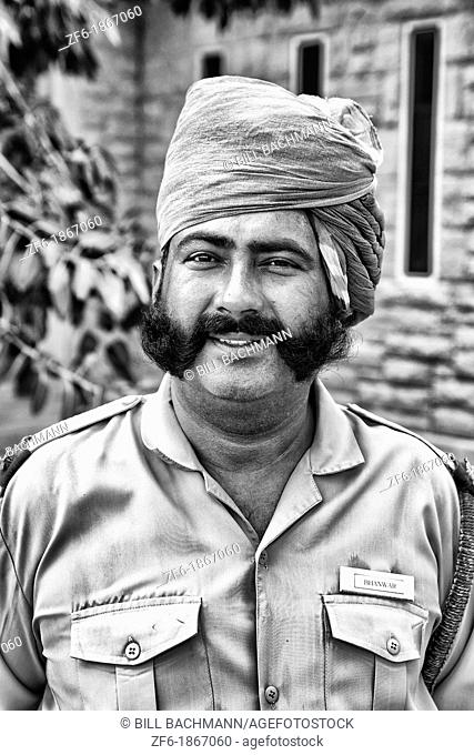 Guard at entrance to the historic Umaid Bhawan Palace in Jodhpur Rajasthan India which is now mostly a hotel where visitors and Raj with Queen now live