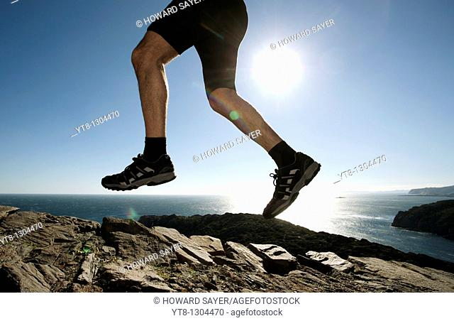 Man running along a rocky coastal path