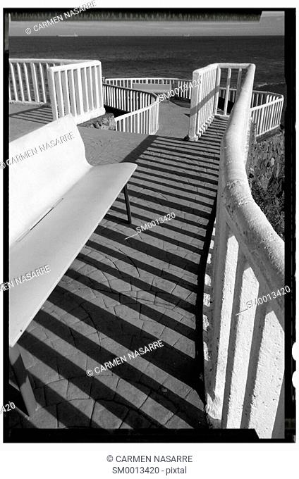 Shadows cast by railing stone lookout over the Bay of Biscay