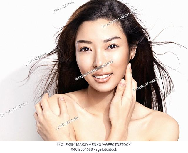 Beauty portrait of a young smiling asian woman face with flying hair isolated on white background