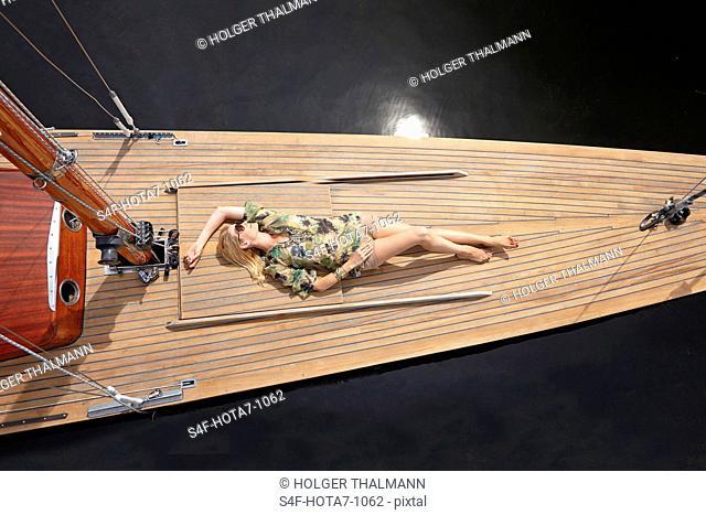 Deutschland, Bayern, Starnberger See, Frau liegt auf dem Deck eines Segelboots