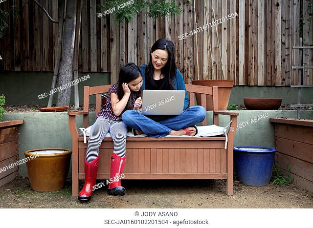 Mother and daughter (6-7) on garden sofa using laptop