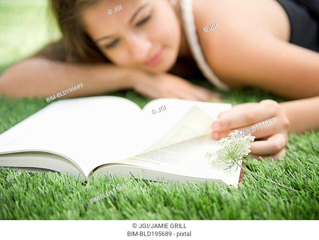 Indian woman laying in grass reading book