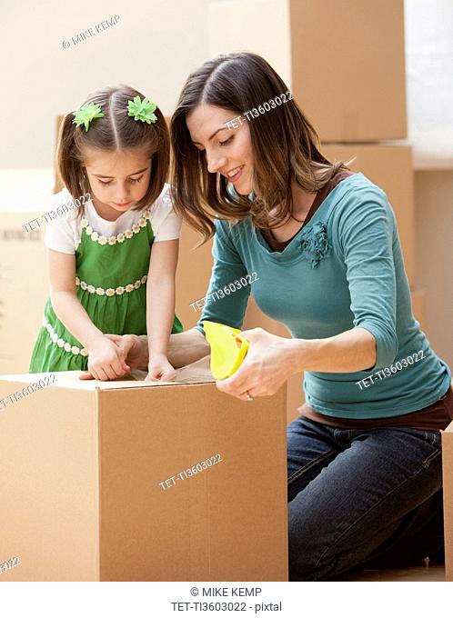 Mother with daughter 4-5 closing cardboard box