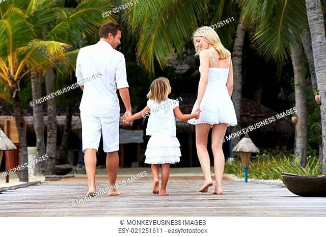 Rear View Of Family Walking On Wooden Jetty