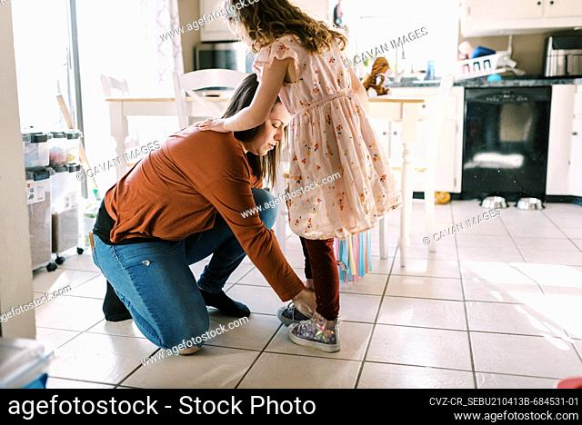 mother helping her daughter put on shoes with laces in kitchen