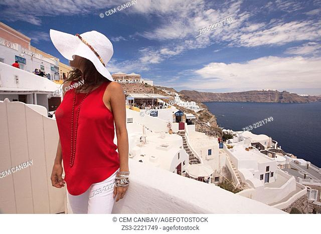 Woman posing at the balcony with the sea, restaurants and hotels at the background, Oia town, Santorini, Cyclades Islands, Greek Islands, Greece, Europe