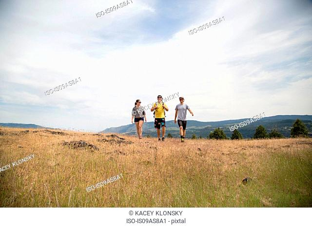 Small group of friends hiking through field