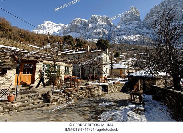 View of Mikro Papingo village and snowy mountains. Mikro Papingo, Ioannina, Epiros, Greece, Europe