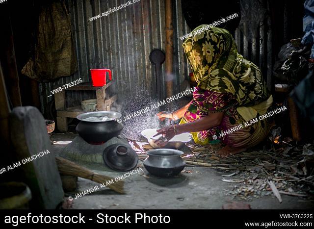 A woman is cooking rice balls on a traditional charcoal-burning clay stove at Narsingdi, Bangladesh