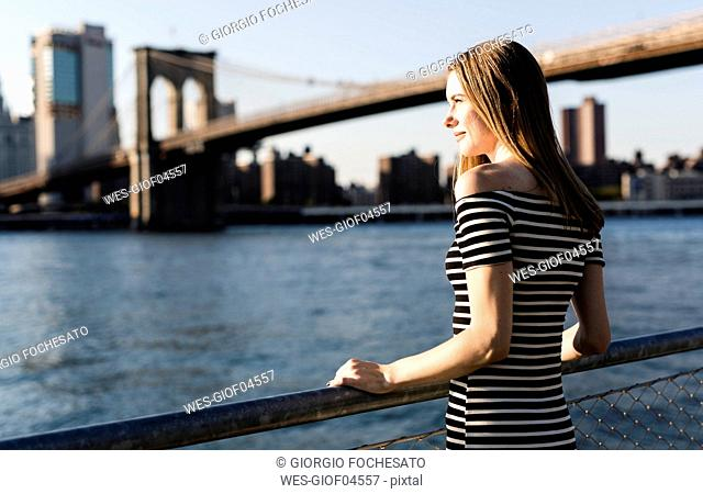 USA, New York, Brooklyn, woman wearing striped dress standing in front of East River by sunset