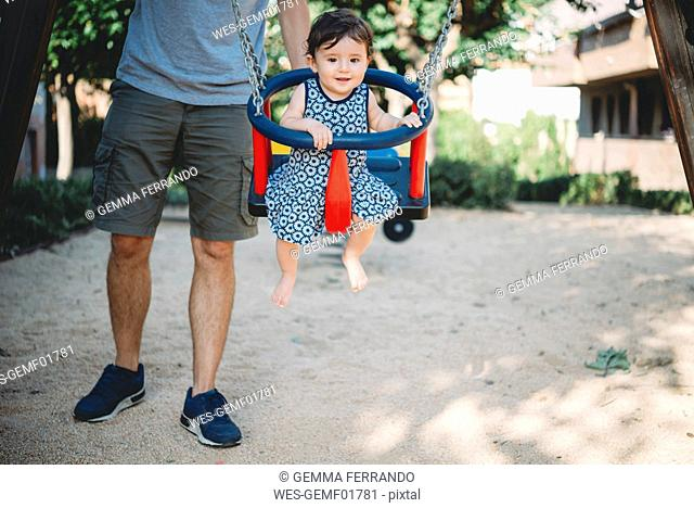 Father swinging his baby girl sitting in swing on playground