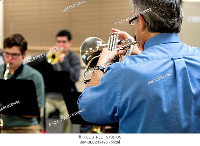 Caucasian music teacher playing trumpet