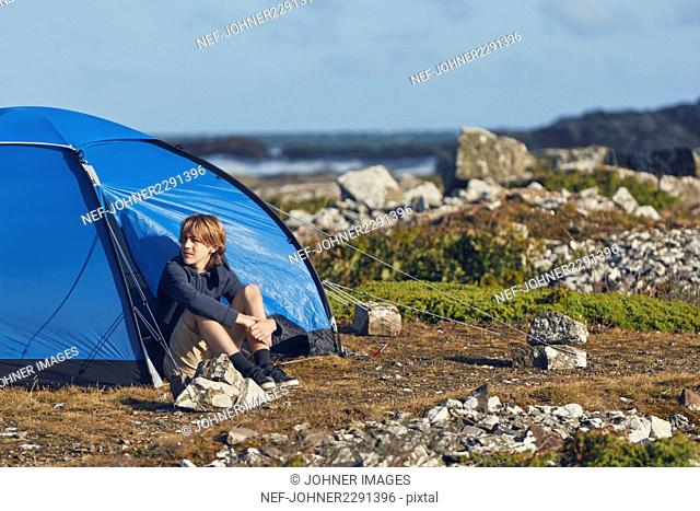 Young man sitting near tent