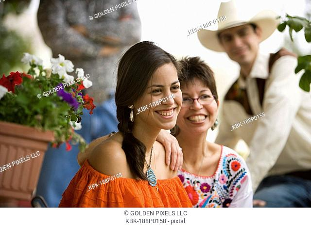 Portrait of a cheerful Tex-Mex family in front porch of house