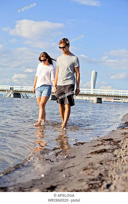 Full length of happy young couple holding hands while walking in sea
