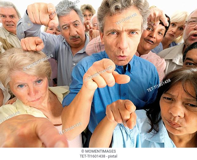 A group of people pointing their fingers in accusation