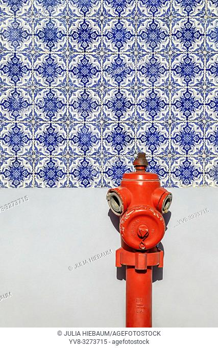 Red fire hydrant in front of a tiled wall in Lisbon, Portugal