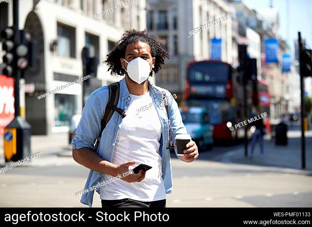 Portrait of young man wearing protective mask crossing the street, London, UK