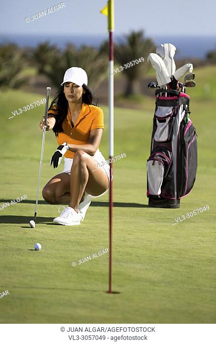 Stylish and confident woman in sportswear sitting on green course with golf driver in bright sunshine