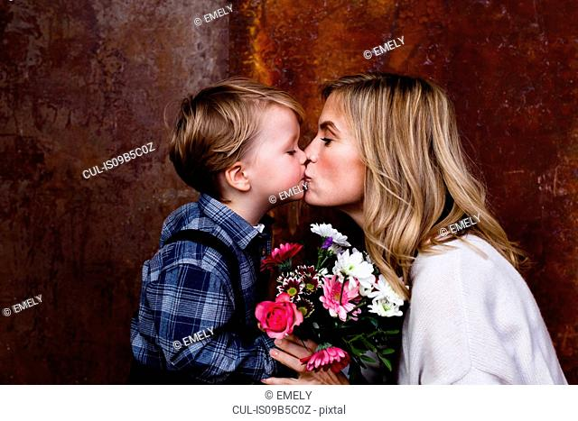 Young boy giving bunch of flowers to mother, mother kissing boy
