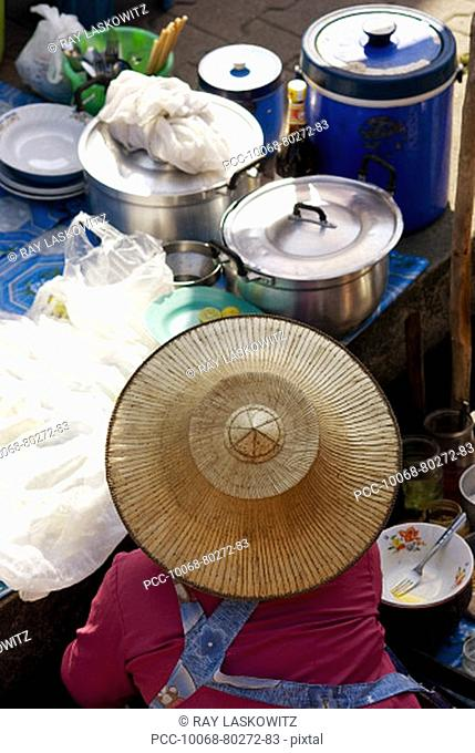 Thailand, Bangkok, View from above of a street food stall with vendor wearing straw hat