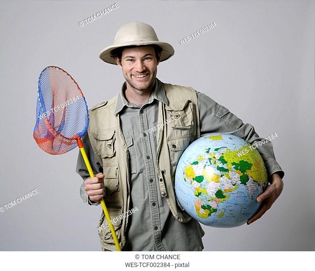 Young man holding globe and fishing net against white background, smiling