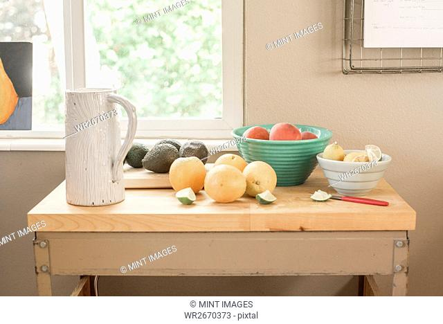 A kitchen table by a window, fresh fruit and avocados in bowls