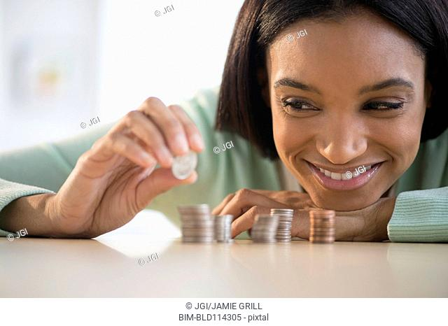 Mixed race woman stacking coins