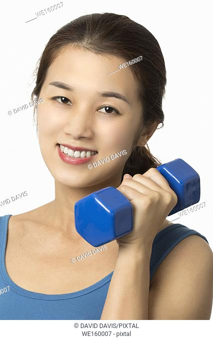 Beautiful Asian woman working out using dumbbell weights isolated on a white background