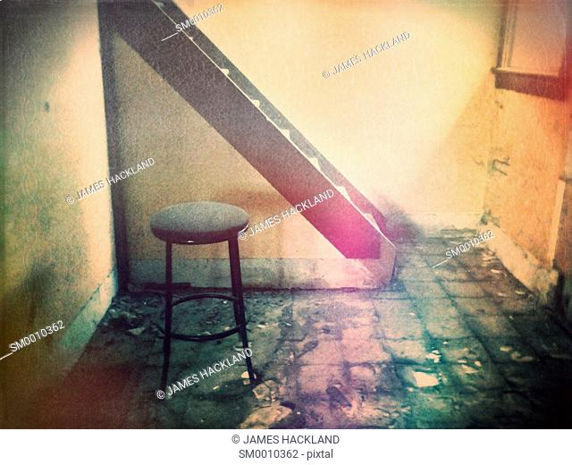 A stool sits on a grungy floor in front of a staircase in a an abandoned house. Ontario, Canada