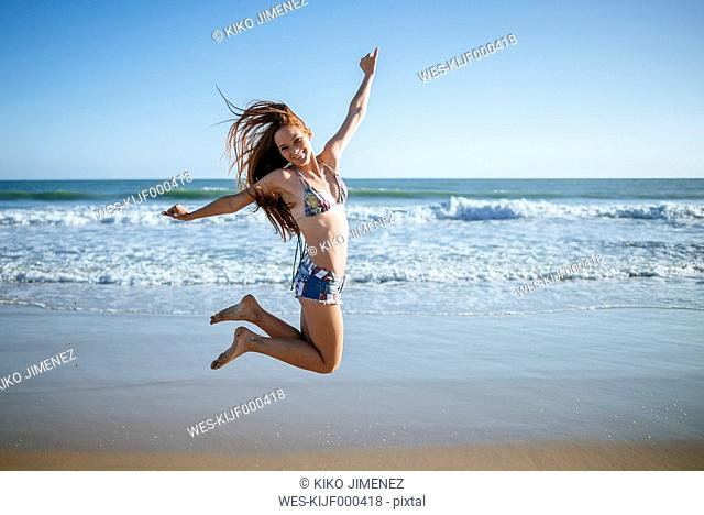 Enthusiastic young woman jumping on beach