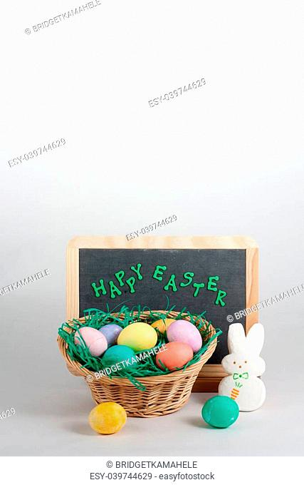 Chalkboard With Happy Easter Words and Wicker Basket of Multicolored Easter Eggs and Marshmallow Bunny