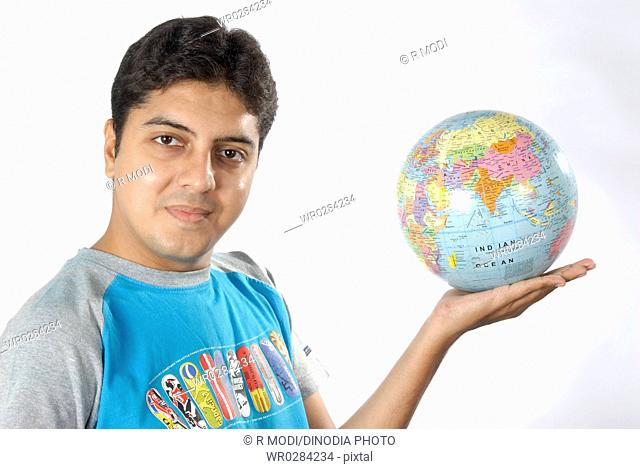South Asian Indian man showing globe and map of India to predict world in his hand MR628