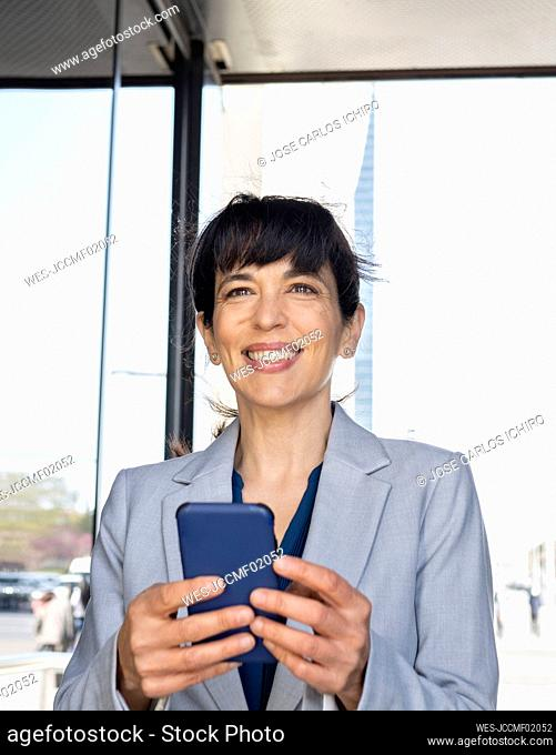 Female professional smiling while holding mobile phone at entrance
