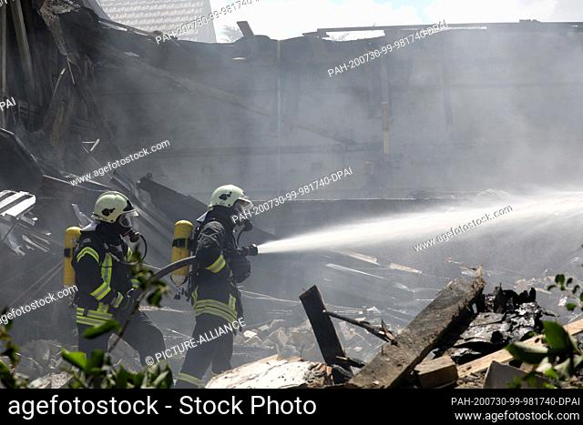 30 July 2020, Mecklenburg-Western Pomerania, Ribnitz-Damgarten: Firefighters extinguish the fire in a large hall of a former furniture manufacturer