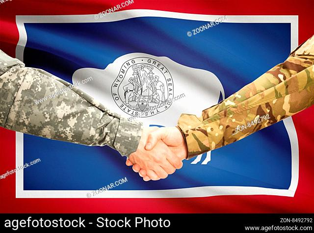 Soldiers handshake and US state flag - Wyoming