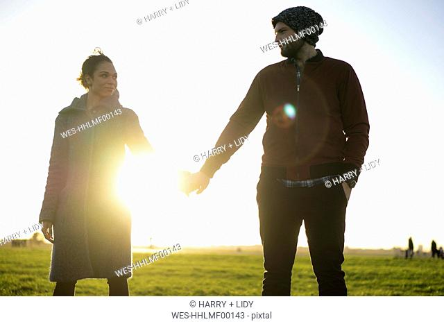 Affectionate young couple standing hand in hand on a meadow at sunset