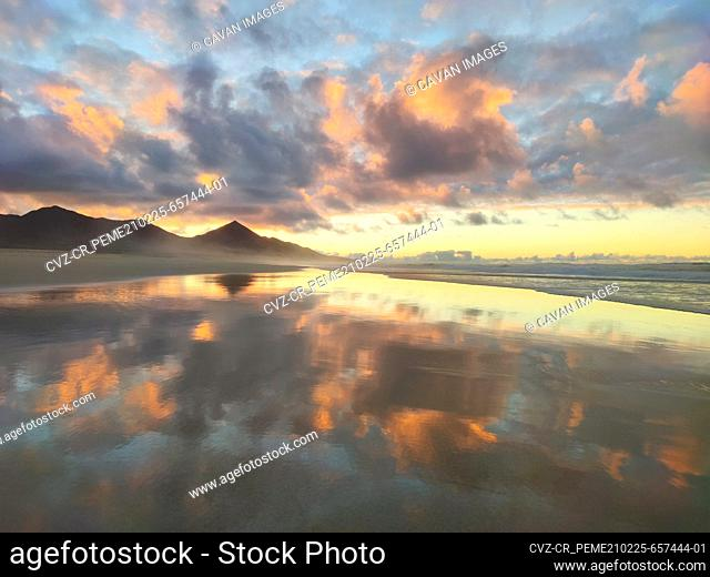 Cofete beach beautiful sunset with a colorful sky and the reflects on the water. Fuerteventura, Canary island, Spain