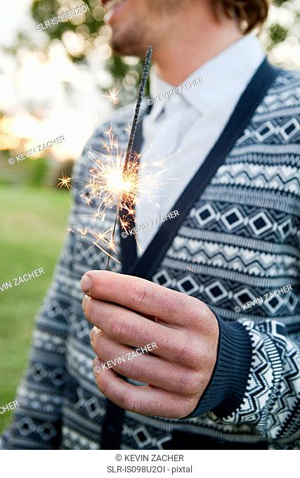 Young man holding a sparkler