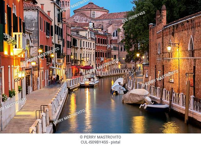 Tolentini Canal with moored boats, Renaissance architectural style residential palace buildings illuminated at dusk, Santa Croce district, Venice, Veneto, Italy