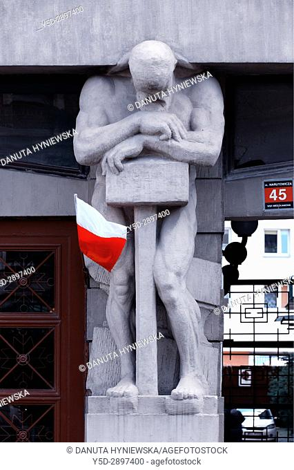 Atlante with Polish flag- one of five full size statues in entrance to tenement house Narutowicza street number 45 built in 1913, Lodz, Poland, Europe