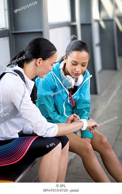 MODEL RELEASED. Two young women sitting on railway platform checking watch