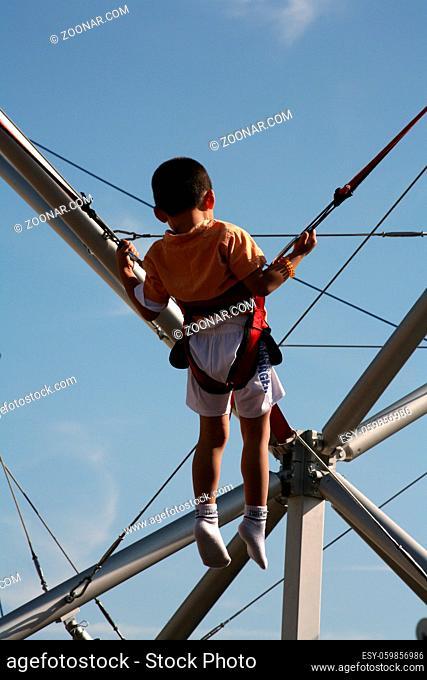 Kleiner Junge auf einem Bungee-Trampolin auf enem Volksfest