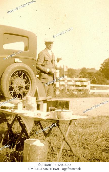 A man wearing formal attire holds a tea cup and stands behind his automobile, with a camp table set up with various bowls in utensils in the foreground