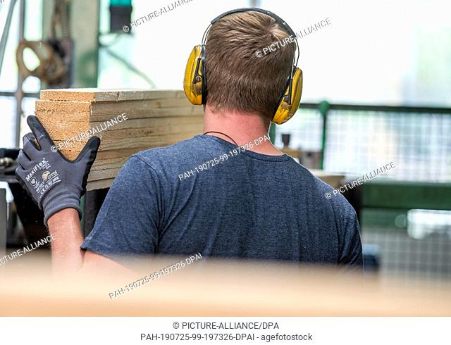 24 July 2019, Mecklenburg-Western Pomerania, Wismar: An employee places wooden boards for the production of new wooden pallets at the company Paletten-Service...