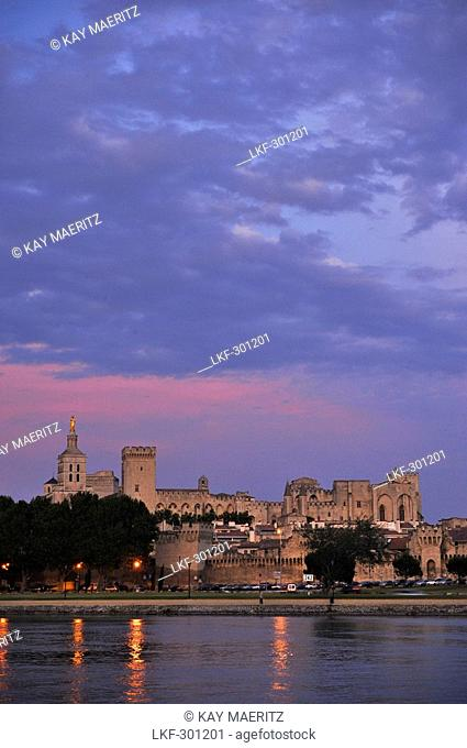 View over river Rhone to city walls, cathedral Notre-Dame-des-Doms and papal palace in the afterglow, Avignon, Vaucluse, Provence, France, Europe