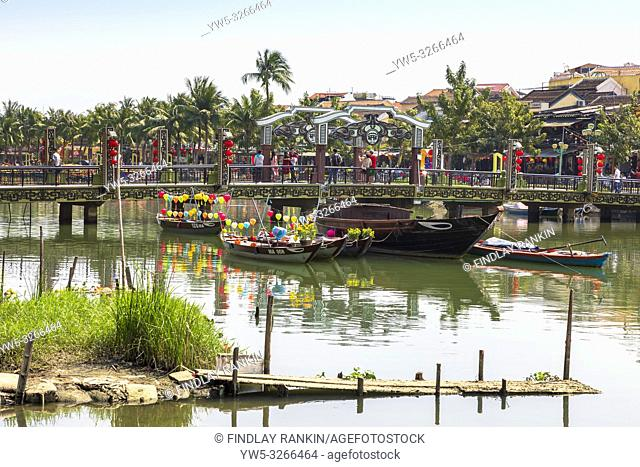 An Hoi bridge over the Son Thu Bon river in, Hoi An, Quang Nam Provence, Vietnam, Asia with lantern boats tied up at the parapet