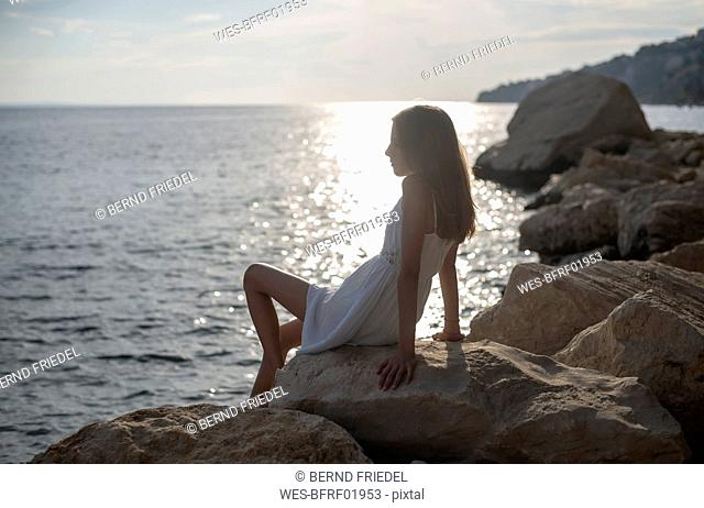 Croatia, Lokva Rogoznica, girl sitting on a rock at dusk looking at distance